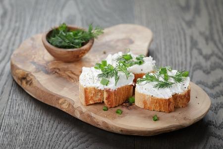 queso: rebanadas de pan crujiente con crema de queso y hierbas en la tarjeta de oliva Foto de archivo