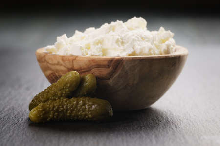 marinate: ricotta cheese in wooden bowl with marinate cucumbers on slate board Stock Photo