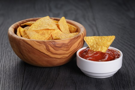 nachos: tortilla chips in olive wood bowl on wooden table, selective focus Stock Photo
