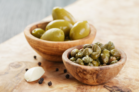olive green: green huge olives and capers on wood table, shallow focus