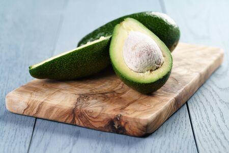 half  cut: ripe avocado half cut on cutting board, close up photo Stock Photo