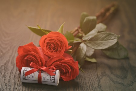 rubberband: three red roses and bunch of dollars, vintage toned Stock Photo