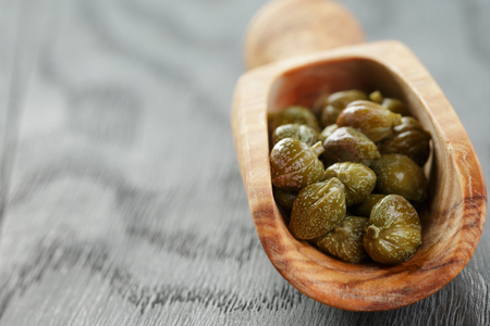 marinated capers in olive scoop on wood table, shallow focus