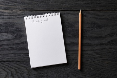 shopping list phrase in notepad on gray wood table, top view Stockfoto