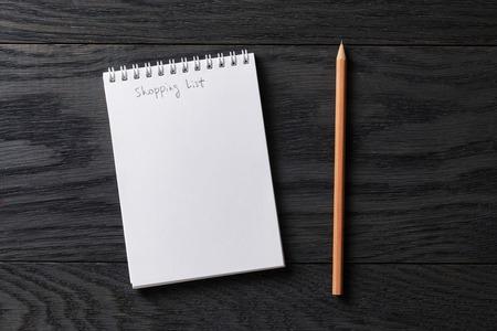 compras: compras frase lista en la libreta en el vector de madera gris, vista desde arriba