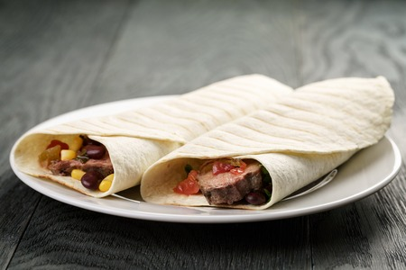 mexican food: burritos with beef steak, corn, black beans and salsa sauce on wood table, shallow focus