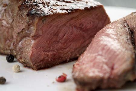 dinner restaurant: sliced beef steak on white plate close up, shallow focus