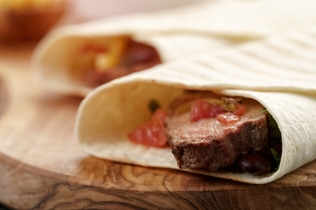 stil: closeup photo of fresh homemade burritos with beef on wood board, shallow dof Stock Photo