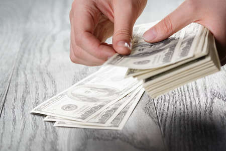 young female hands count dollar bills on wood table, closeup photo Stock Photo
