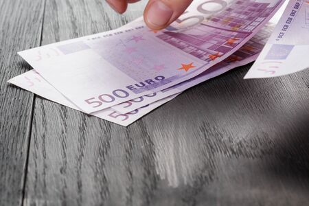 euro banknote: young female hands count euro bills on wood table, closeup photo