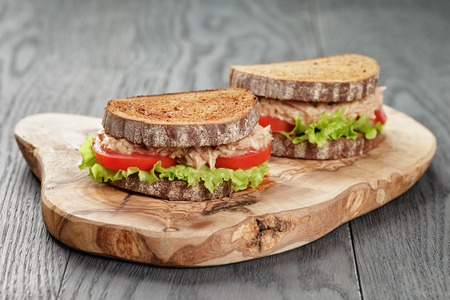 rye bread sandwich with tuna and vegetables on wood background