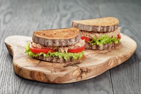 bocadillo: s�ndwich de pan de centeno con at�n y verduras en el fondo de madera