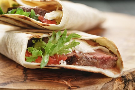 Stil: fresh homemade burritos with beef on olive cutting board shallow dof