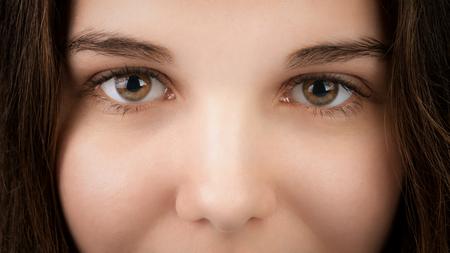 hazel eyes: closeup portrait of young woman with hazel eyes, focus on eyes