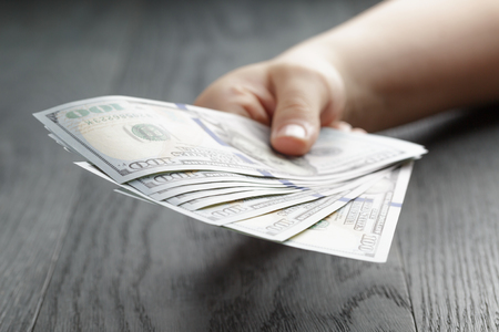 pay money: female teen hand hold dollar banknotes, over wooden table