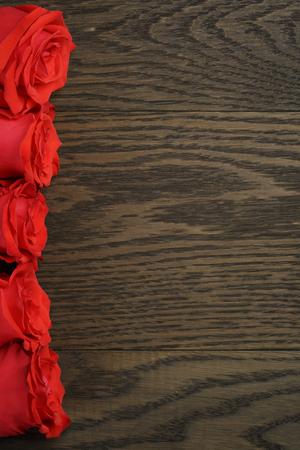 matrimonio feliz: rosas rojas en una fila en la mesa de madera, Vista desde arriba Foto de archivo