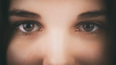 close up eyes: face of a young girl with hazel brown green eyes, dark vintage toned photo