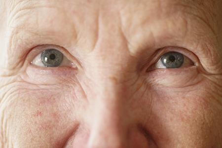 close up eyes: senior woman grandma eyes looking to camera close up portrait, shallow focus