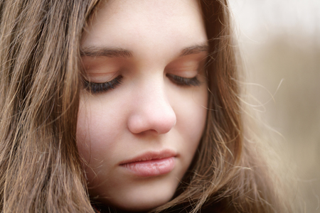 outdoor photo: close up portrait of sad young girl, outdoor photo Stock Photo