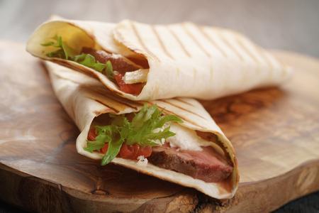 stil: burritos with beef steak, corn, black beans on wood table, vintage toned