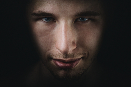 unkind: dark young adult man portrait fade in black background Stock Photo