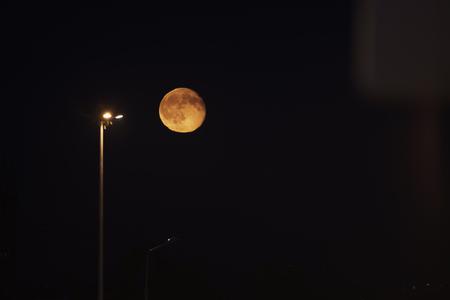penumbra: orange moon in nigh sky over industrial area, full moon