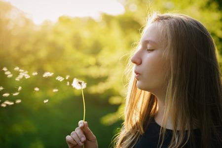 blowing dandelion: teen girl blowing dandelion in sunset light, side view