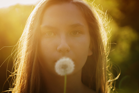 pureness: teen girl ready to blow dandelion to the camera, focus on girl