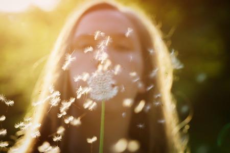 blowing dandelion: teen girl blowing dandelion to the camera, focus on girl