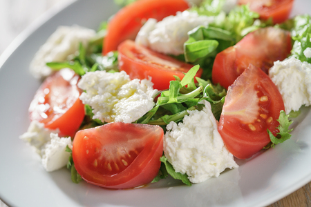 roquette: summer light salad with tomatoes, mozzarella and rocket leaves, shallow focus Stock Photo