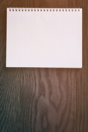toned: blank notepad on wood table, vintage toned