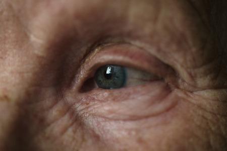 time sensitive: old woman blue-gray eye closeup photo, shallow focus Stock Photo
