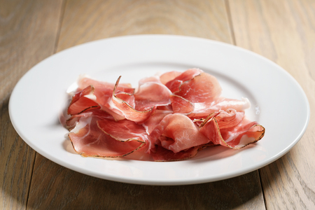 speck slices on white plate on old wood table, shallow focus