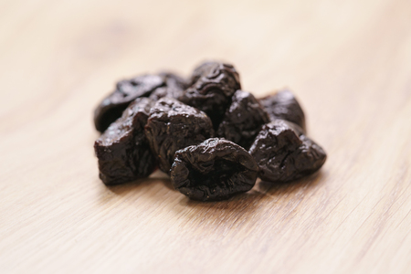 prunes: dried prunes on oak wood table, selective focus Stock Photo