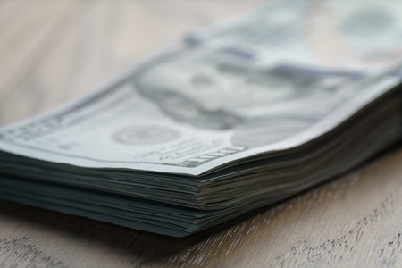 five dollar bill: bunch of dollars on oak wood table, shallow focus Stock Photo