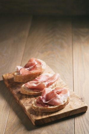 speck: simple ciabatta slices with speck ham on wood table Stock Photo