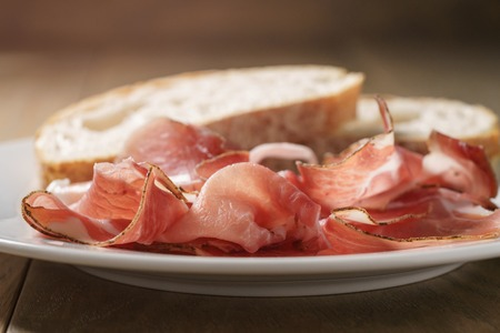 speck: speck slices on white plate with ciabatta on old wood table, shallow focus