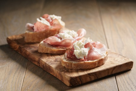speck: simple ciabatta slices with speck and mozzarella on wood table