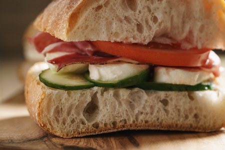 speck: italian ciabatta sandwich with speck and mozzarella, closeup food photo