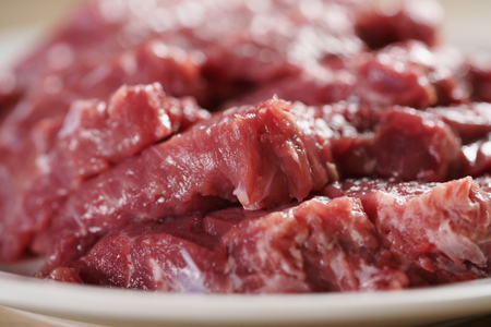 beefsteaks: raw fresh sliced beef for beefsteaks in plate on kitchen table, shallow focus