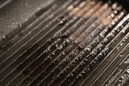 beefsteaks: dirty grill pan after preparing beefsteaks, shallow focus