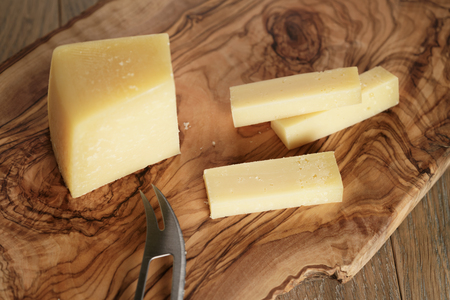 cutted: cutted parmesan cheese on olive cutting board, shallow focus