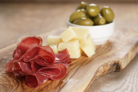 classic italian antipasti, breasola. olives and parmesan on olive board, shallow focus Standard-Bild