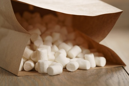 marshmellow: marshmallow in brown craft paper bag on wooden table, shallow focus