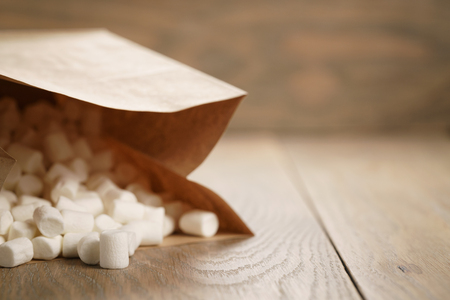 marshmallow in brown craft paper bag on wooden table, shallow focus