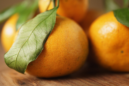 organic fresh tangerines with leaves on wooden table, shallow focus