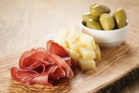 bresaola with parmesan cheese and olives on cutting board, italian antipasti Standard-Bild