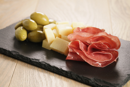 bresaola with parmesan cheese and olives on slate board, italian antipasti