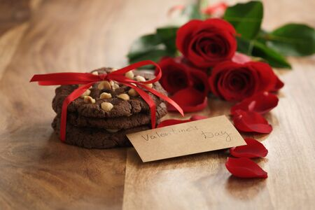 three red roses with homemade chocolate cookies for valentines day, shallow focus