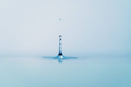 circular water ripple: clear blue water drop with ripple on surface, shot from side with shallow focus